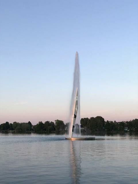 Stor fontän i vattnet i solnedgång