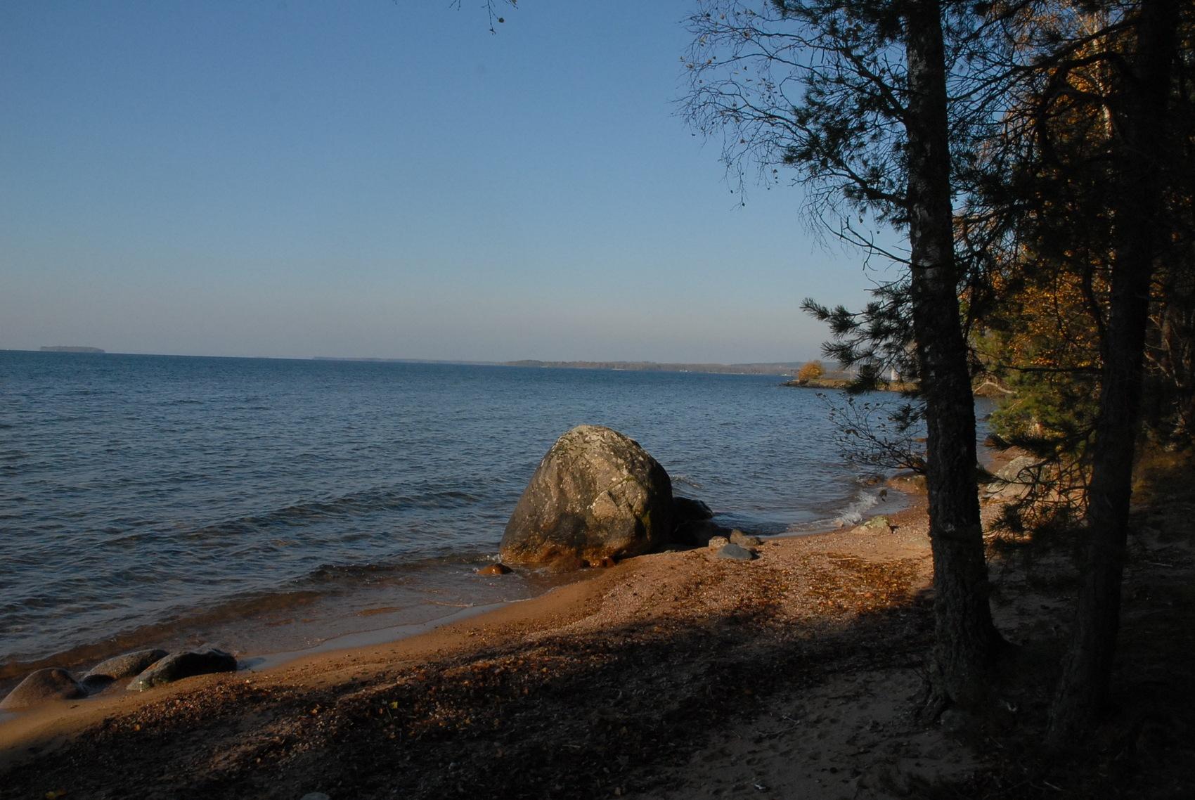 Liten strandkant. I vattenbrynet ligger en stor sten.