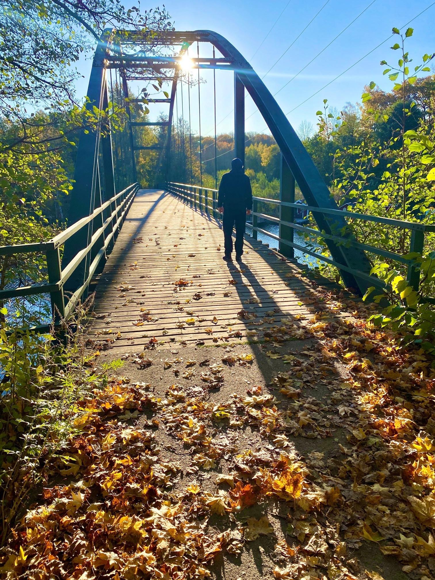 Man går över gammal bro i motljus en höstdag.