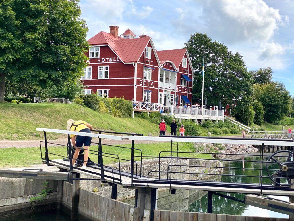 Sluss i Göta Kanal. Slussvakt vevar upp porten.