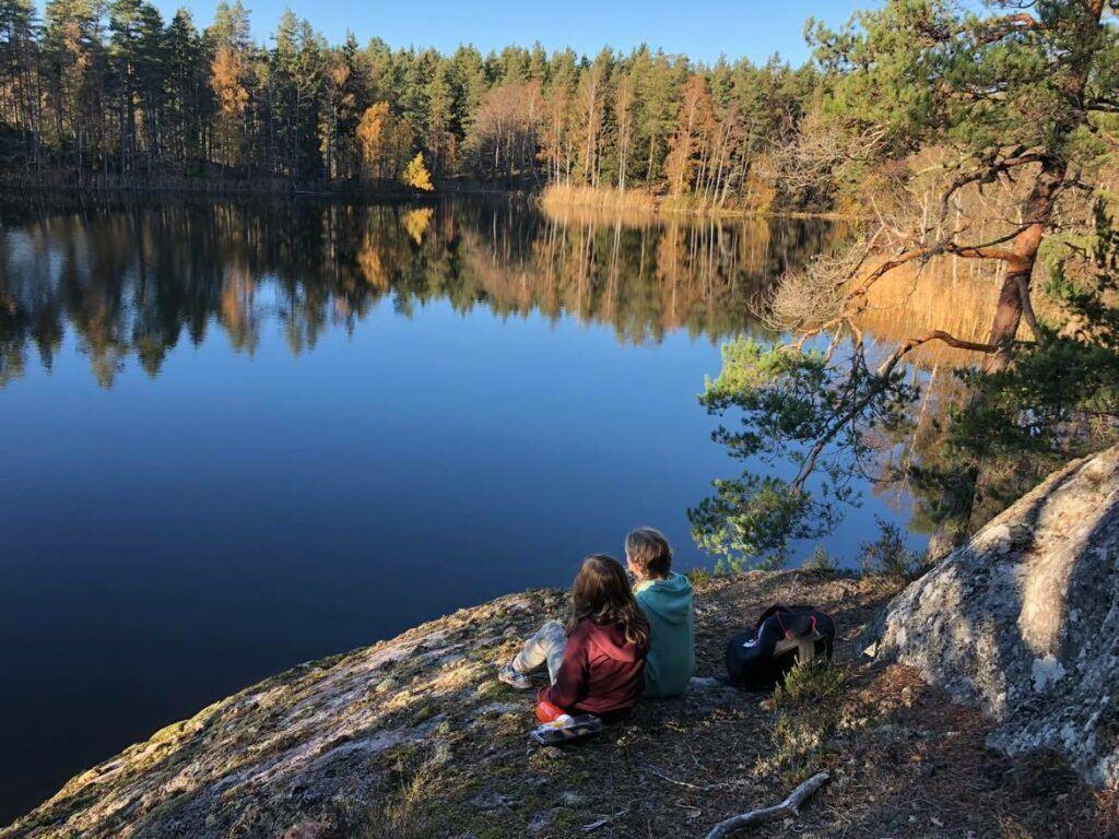 Spegelblank skogsjö. På en klippa sitter ett par och tittar ut över vattnet.