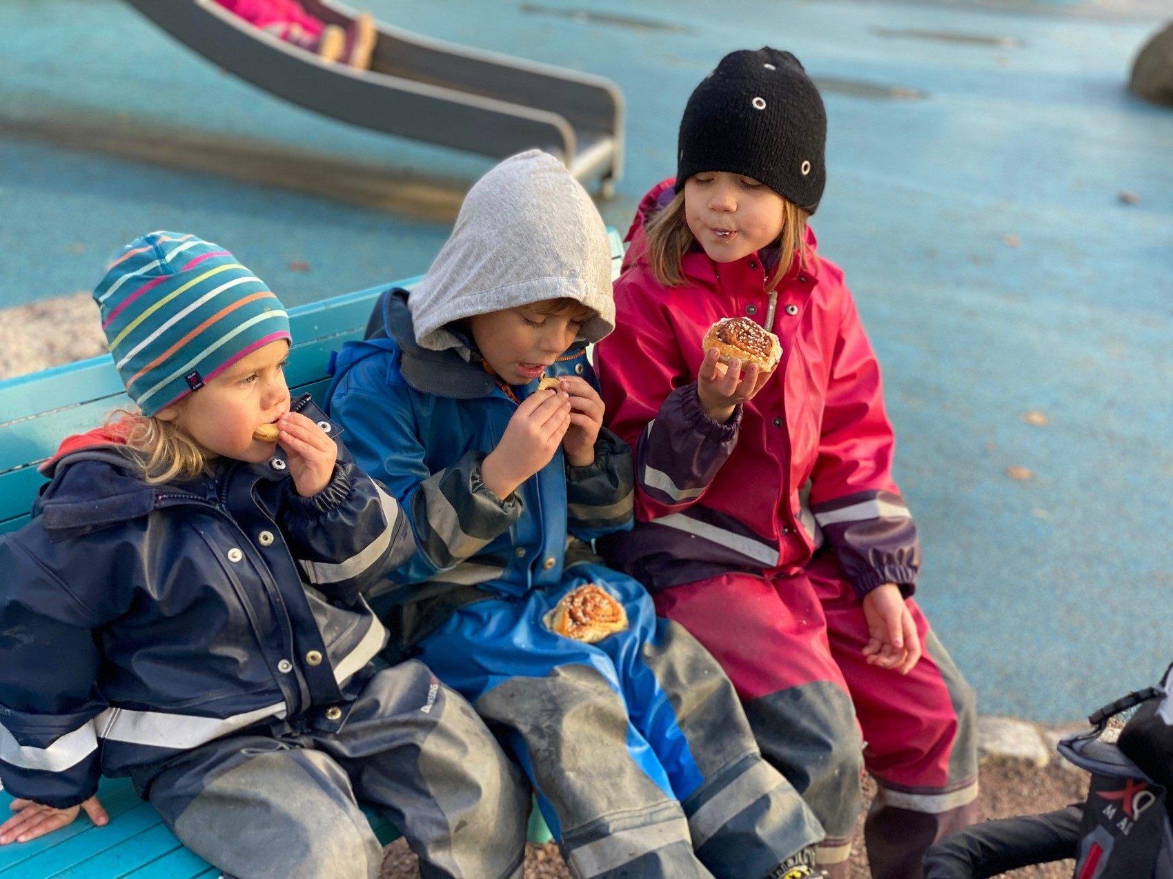 Tre barn i regnkläder fikar i lekpark