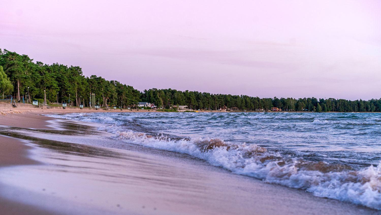 Vågor slår in mot stranden en vacker sommarkväll