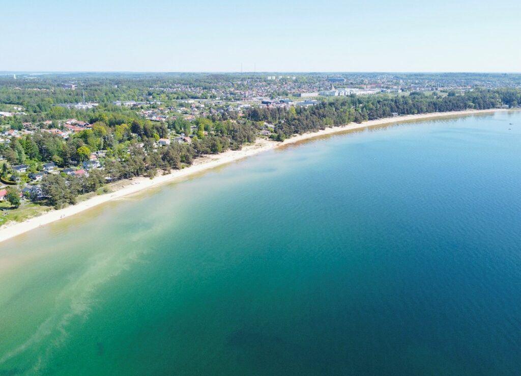 en drönarbild över en lång vit sandstrand intill ett blått vatten