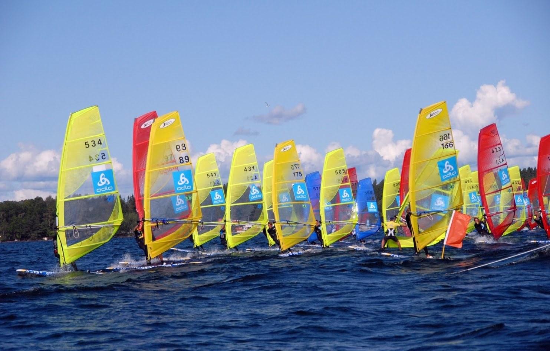 Vindsurfare med färgglada segel ute på vattnet