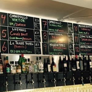 Bar med olika flaskor och en handskriven meny på väggen.