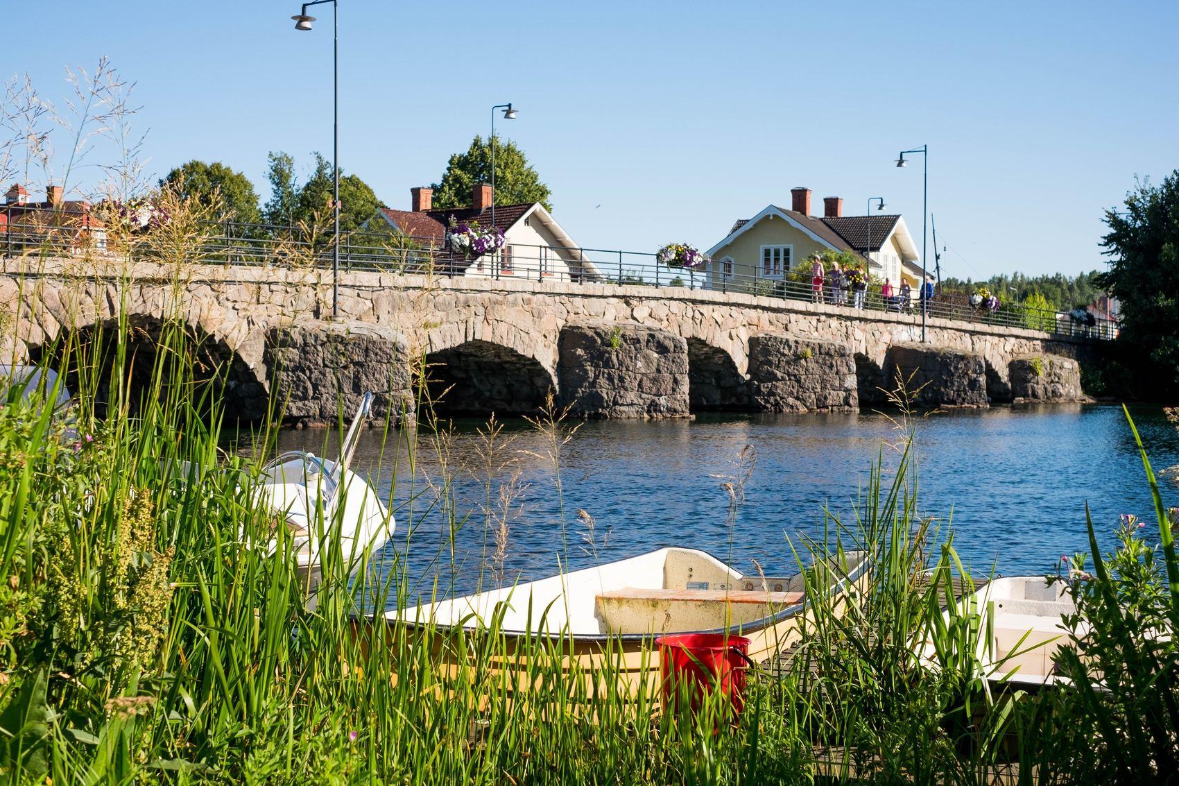 Gammalstenbro över vattendrag. I vattnet ligger båtar.