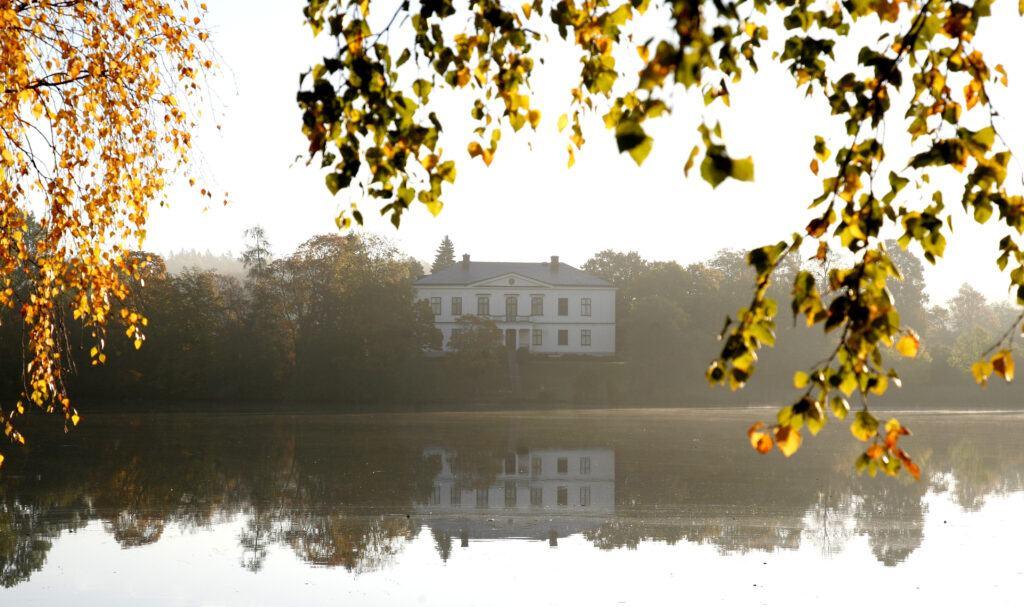 Ett vitt slott med spegelblankt vatten framför.