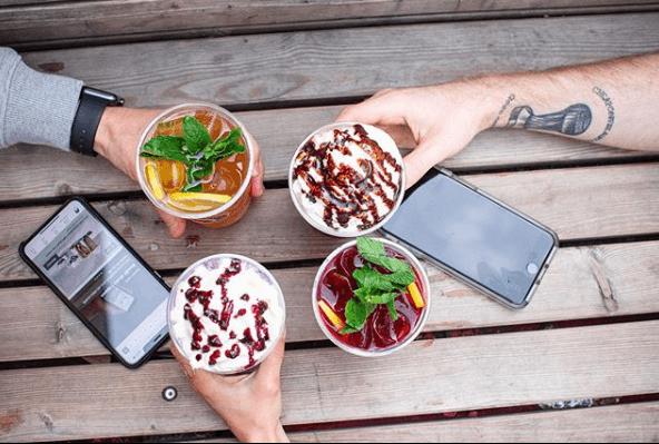 Foto taget uppifrån på tre händer som håller i varsin bägare med glass.