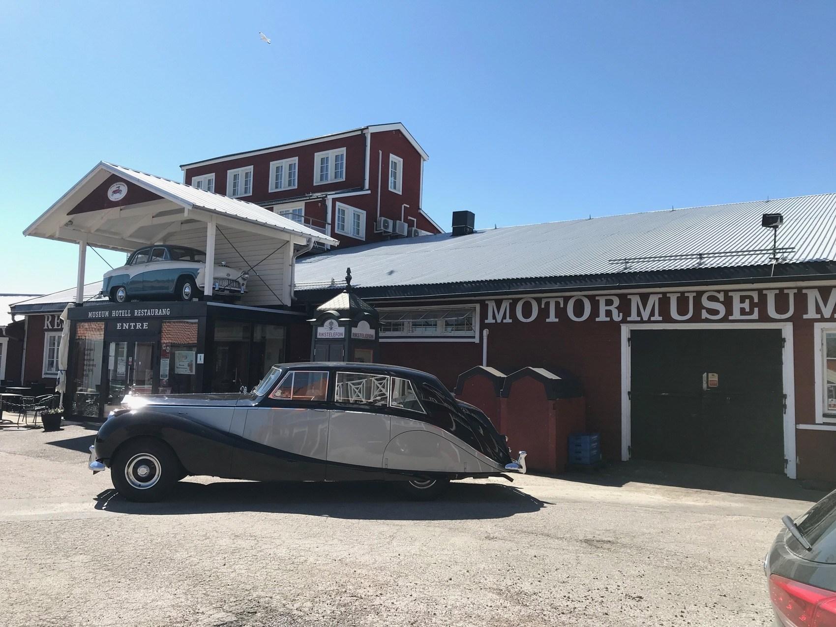 En fin gammal bil står framför Motala Motormuseums entré