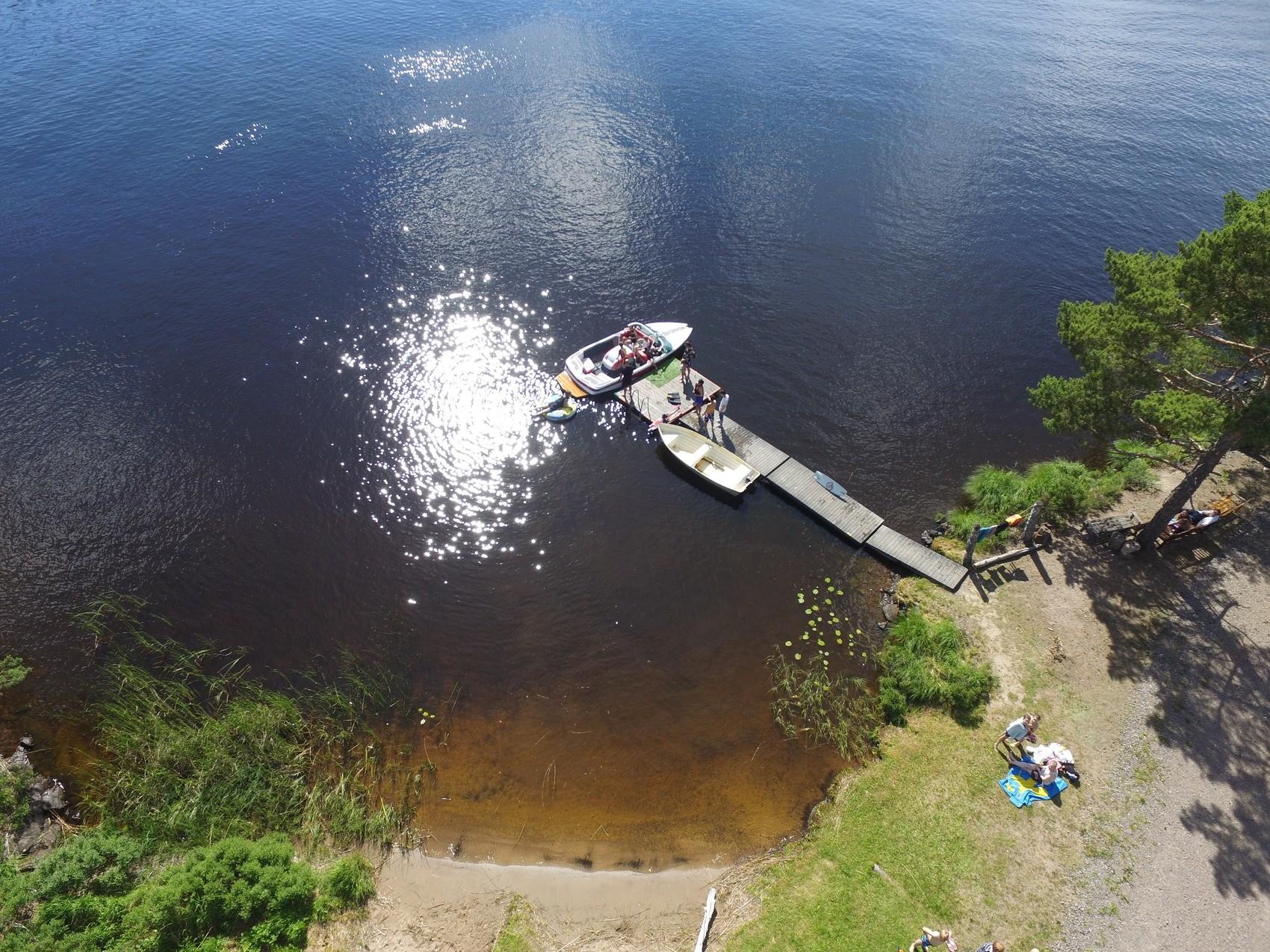 En båt som ligger vid brygga i skogssjö syns ovanfrån.