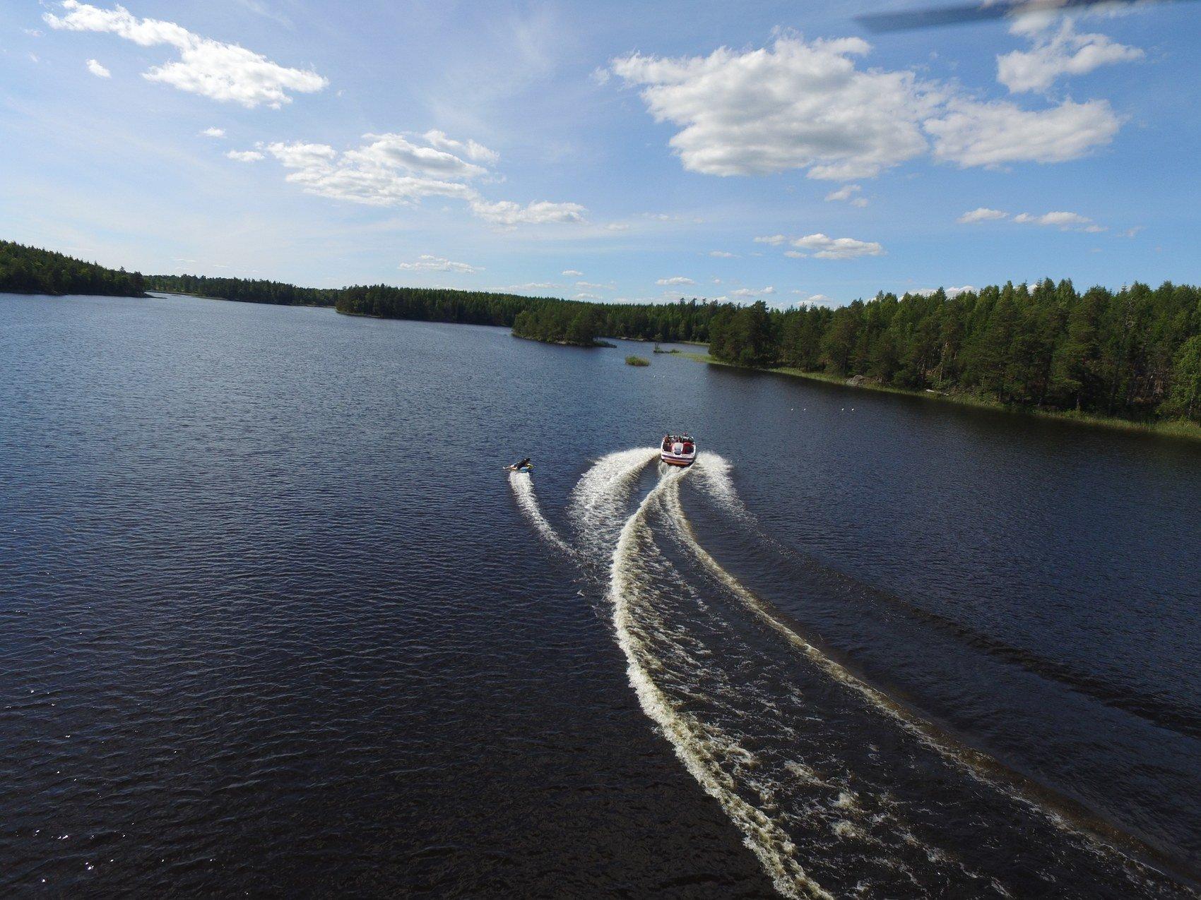 En motorbåt åker i en skogsjö. En person åker vattenskidor.
