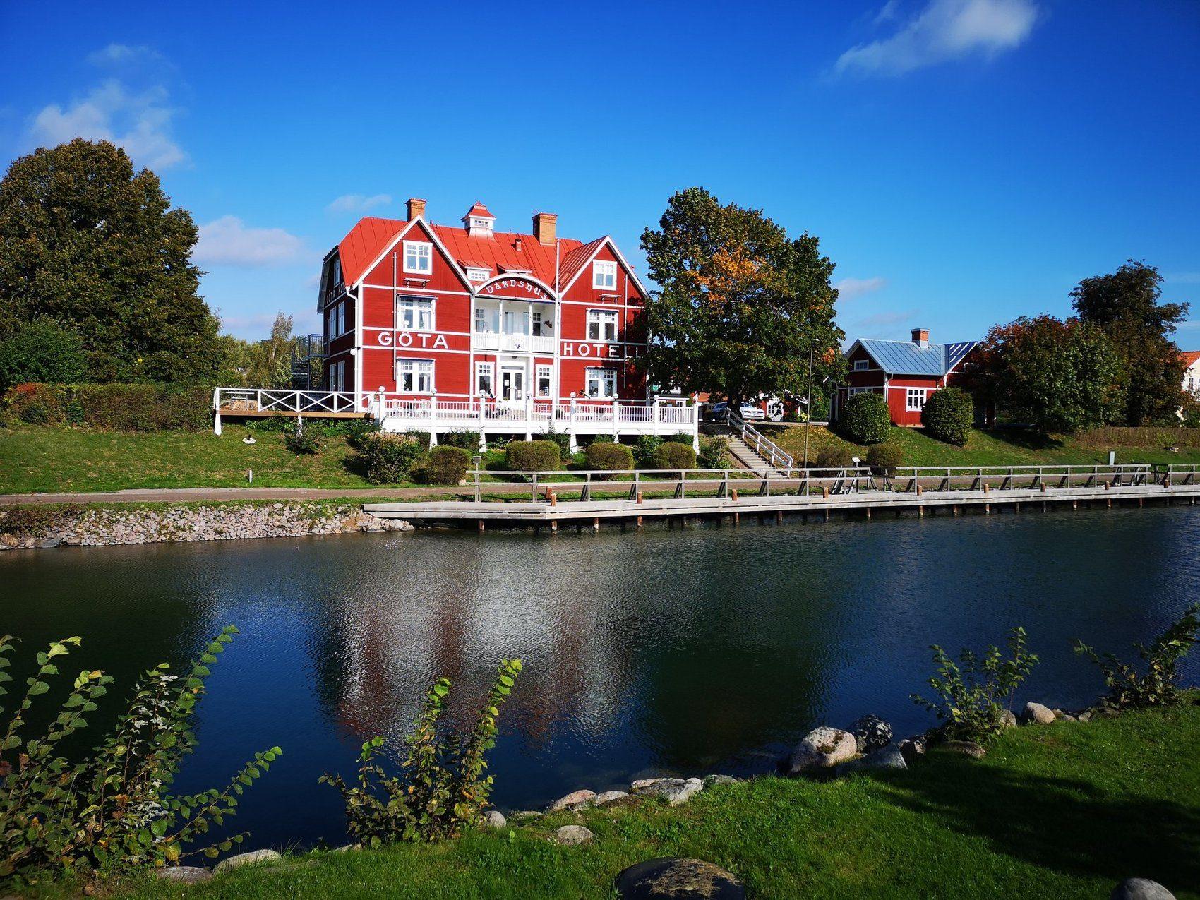 Vacker röd äldre träbyggnad. Framför rinner kanalen.