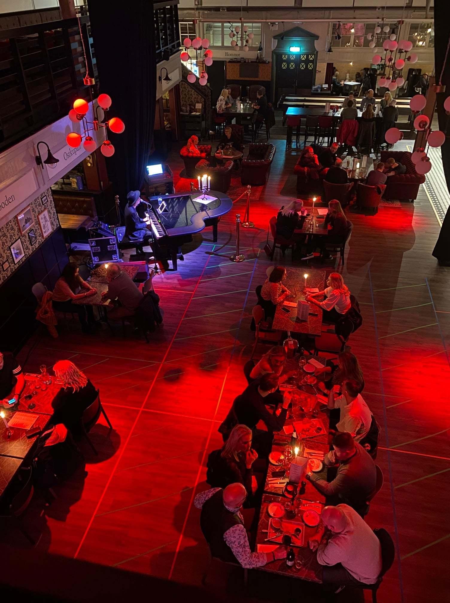Stor lokal sedd uppifrån. Lokalen är upplyst i ett rött sken och människor sitter runt bord.