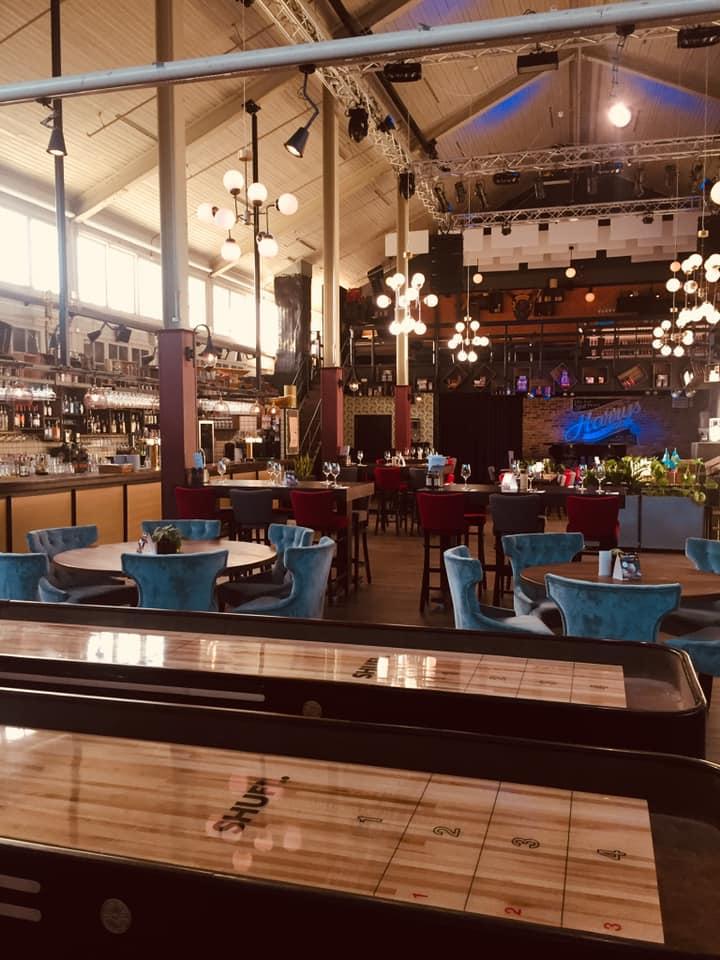 Restauranglokal med högt till tak. Bord med tukosa stolar i sammet står utsprida.