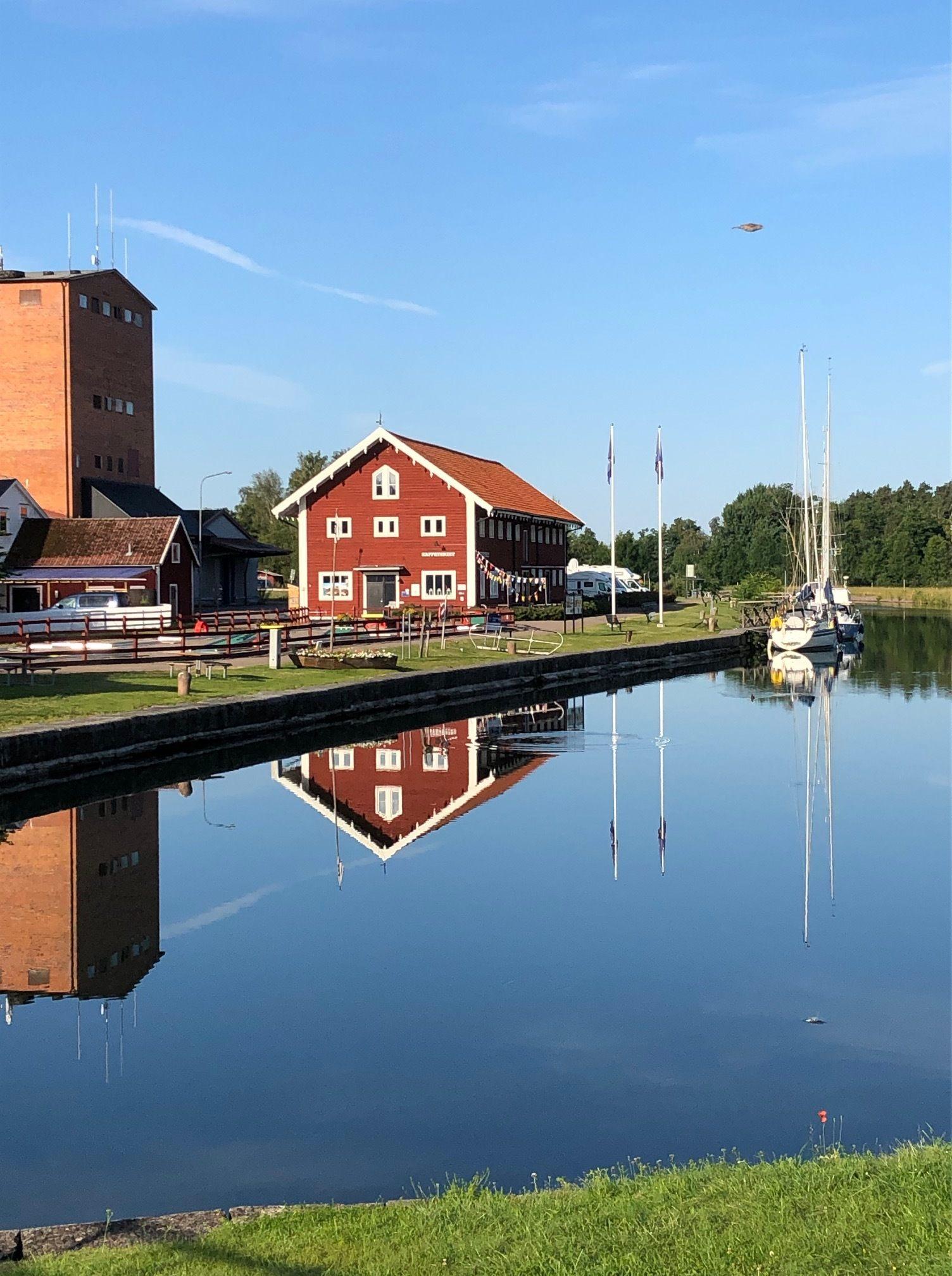 Spegelblankt vatten och klarblå himmel. På andra sidan vattnet ligger en röd byggnad med vita knutar.