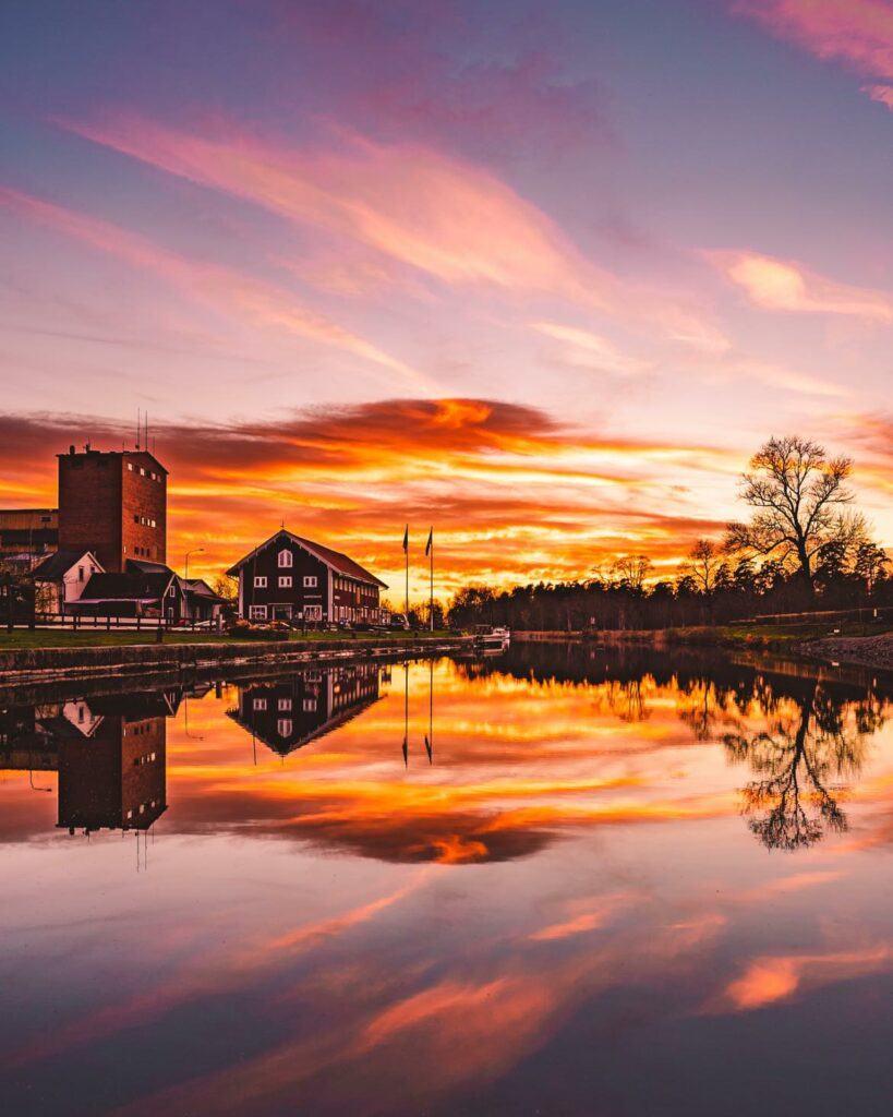 Magisk solnedgång över spegelblankt vatten.