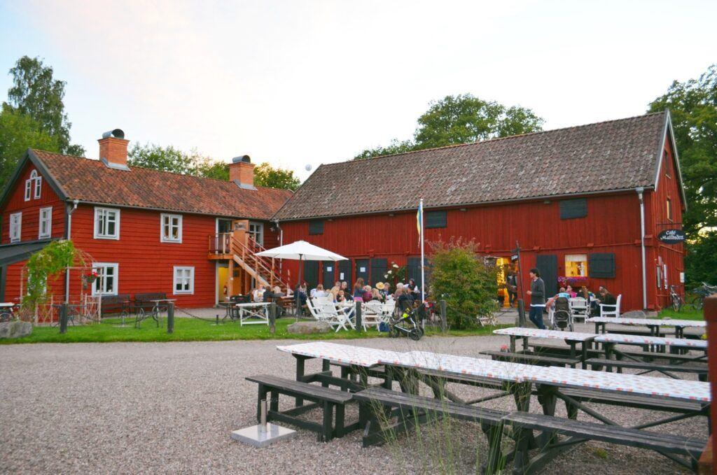 Gårdsplan med café bord framför äldre röda träbyggnader