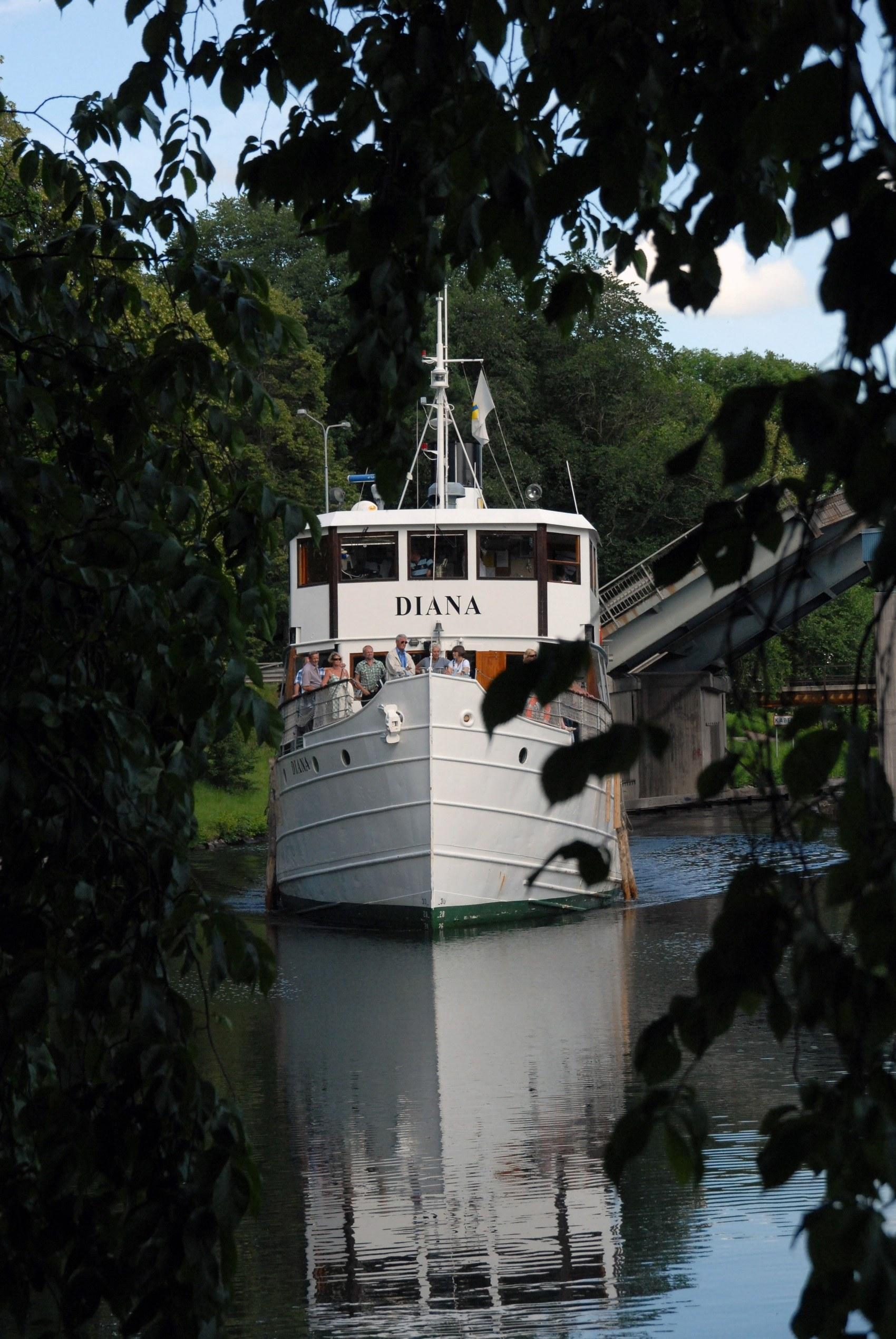 Stor vit passagerarbåt glider fram i Göta Kanal.