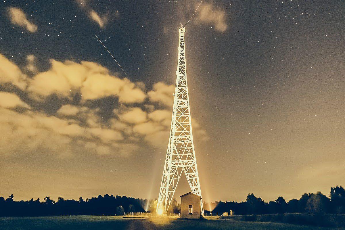 Hög radiomast fotad i mörker med belysning riktad mot masten vilket får effekten av att master ser ut att glöda.