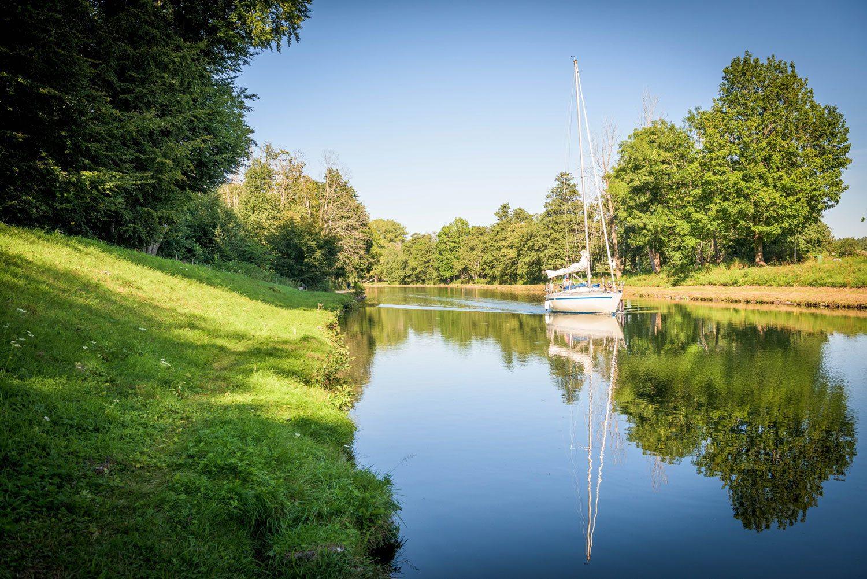 Stor segelbåt glider fram på en spegelblank kanal
