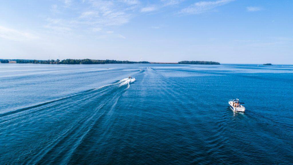 Drönarfoto över klarblått vatten och himmel. I vattnet åker två motorbåtar.