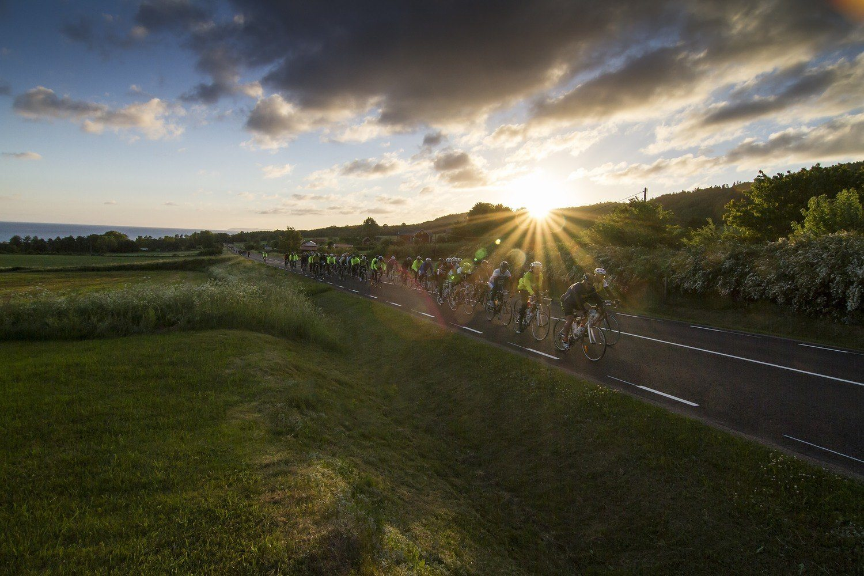 Grupp med cyklister cyklar på landsväg i solnedgång