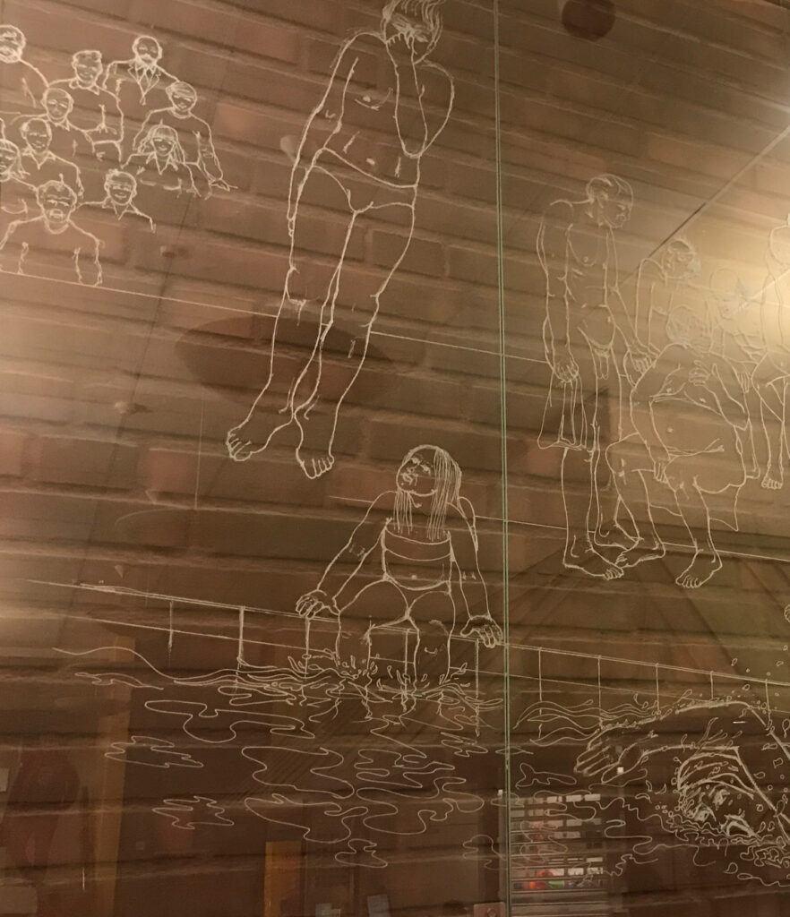 En glasskiva med inristade motiv som hör ihop med en simhall, monterad på en tegelvägg