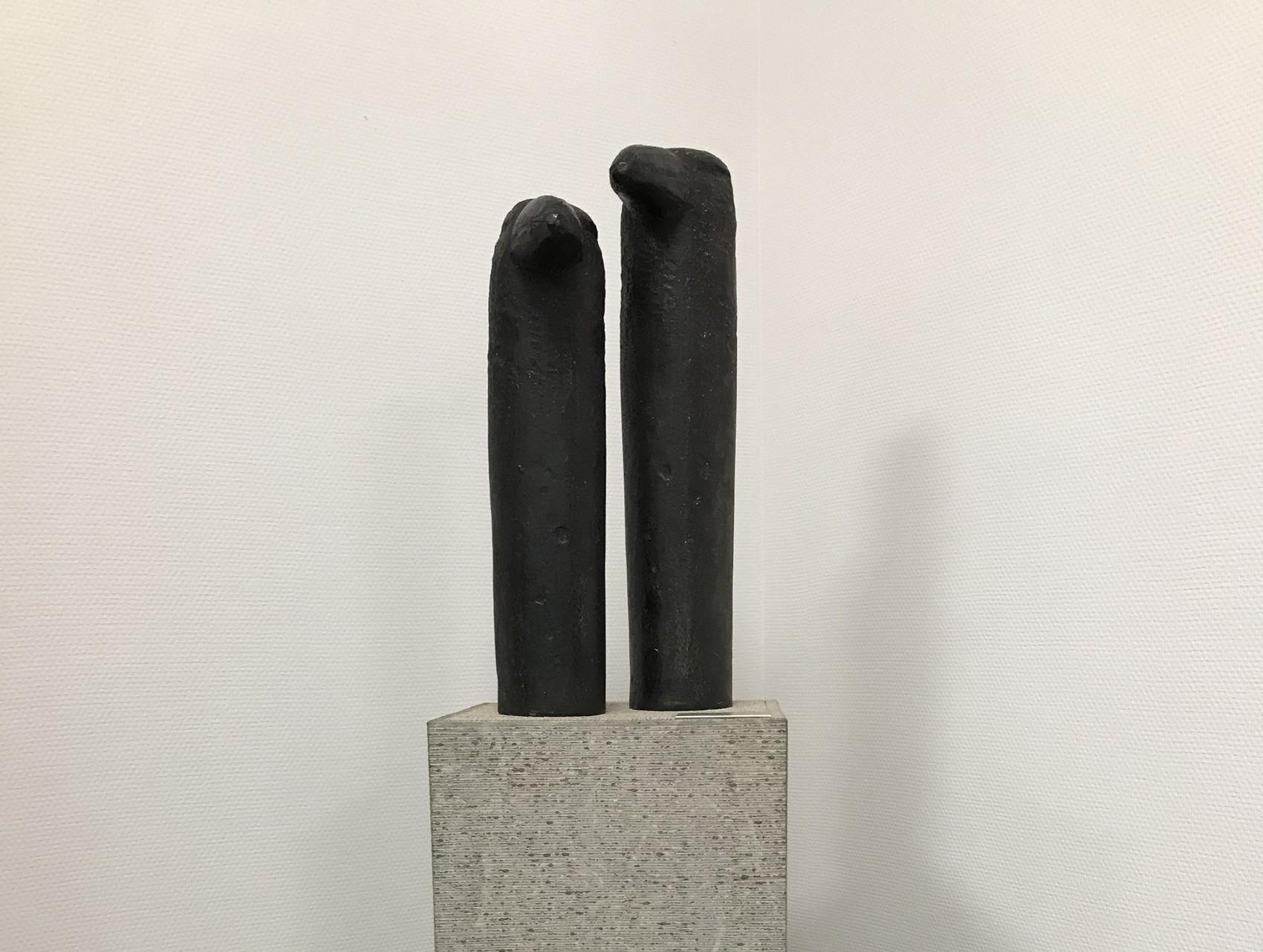 Två svarta cylinerformade figurer med näbbar står på en grå stenstod.