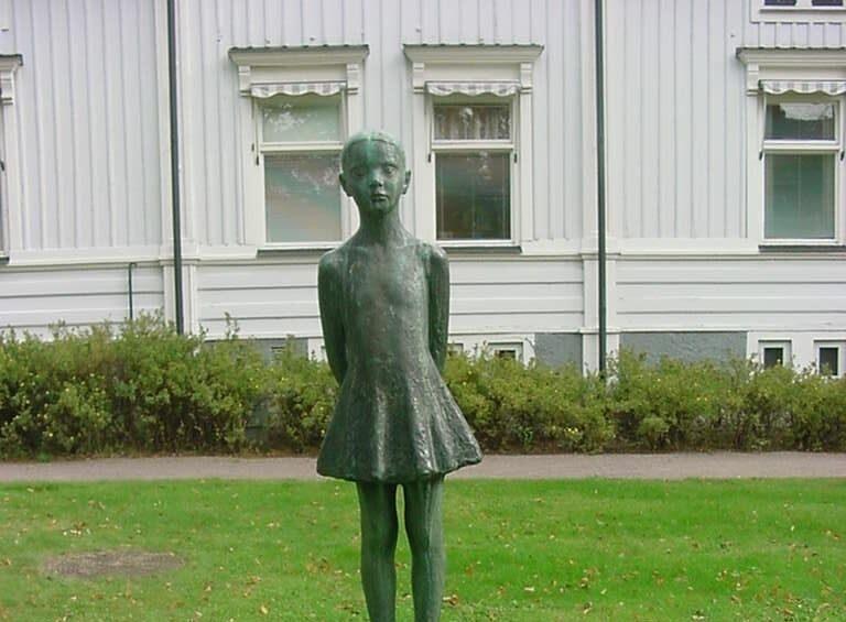 Foto av en staty bestående av en liten flicka som står barfota med armarna bakom ryggen, iförd en klänning.