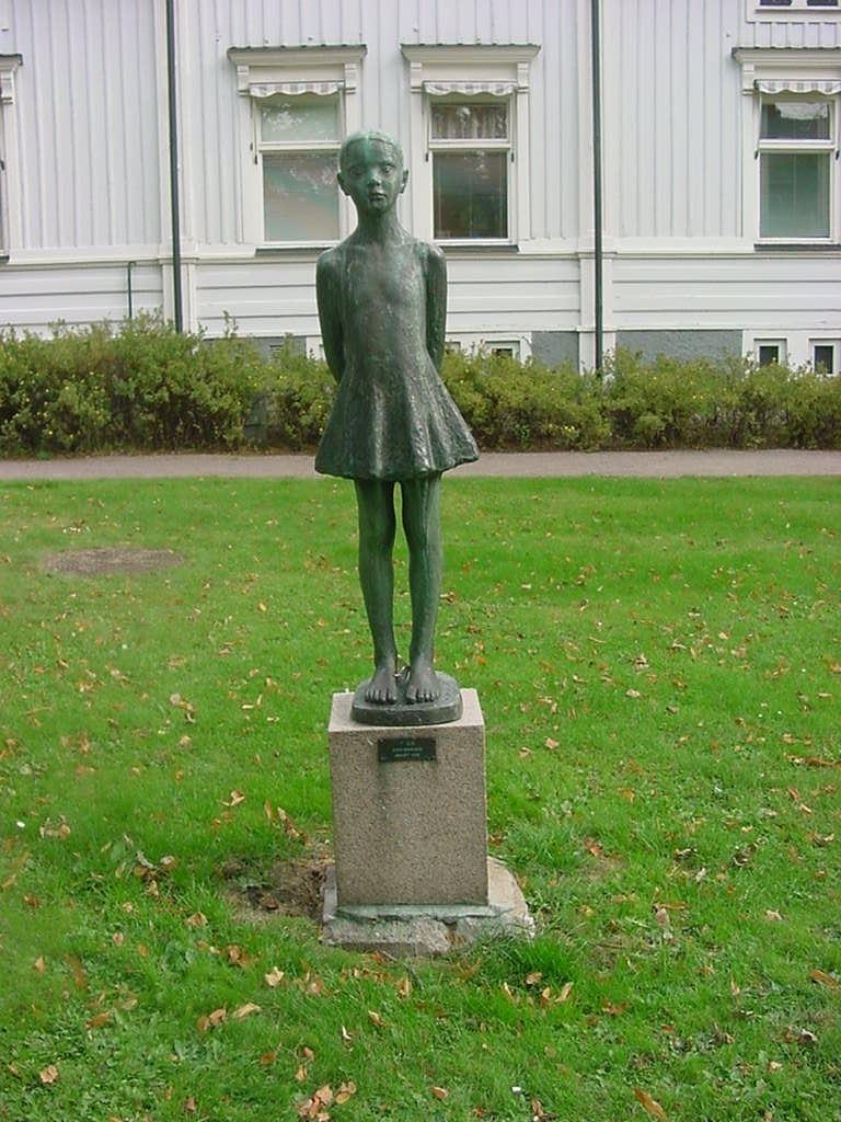 Foto av en staty bestående av en liten flicka som står barfota med armarna bakom ryggen, iförd en klänning. Statyn är placerad på ett stenfundament.
