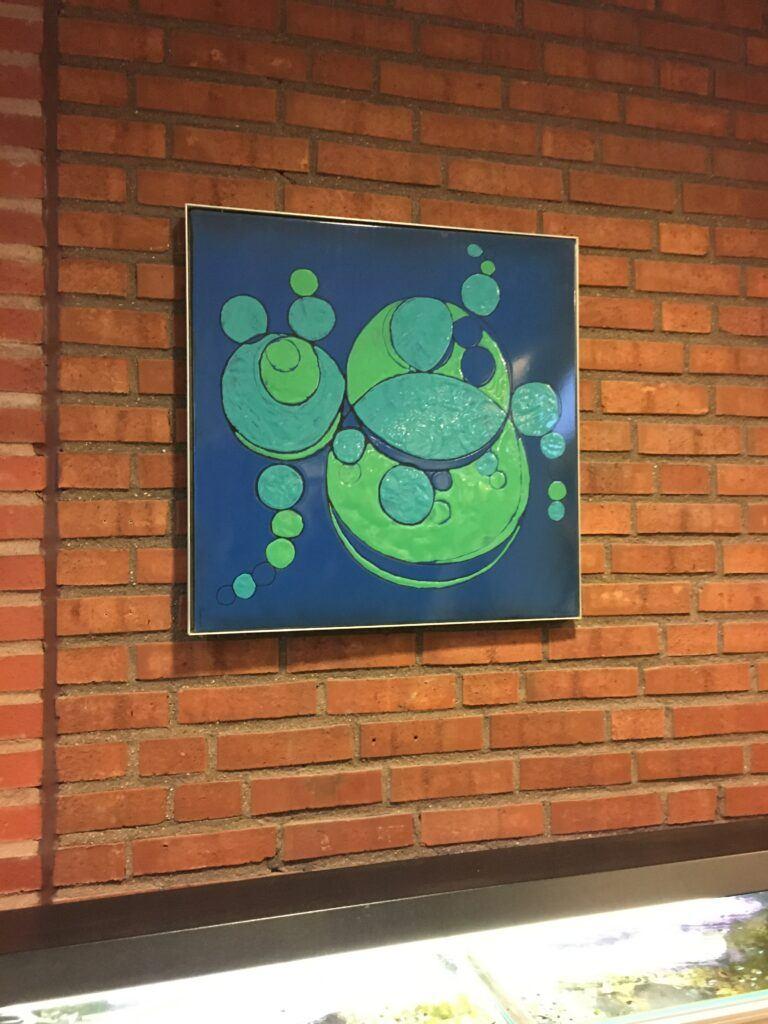 Ett foto av en tegelvägg där det hänger en tavla med mörkblå bakgrund och gröna bubblor.