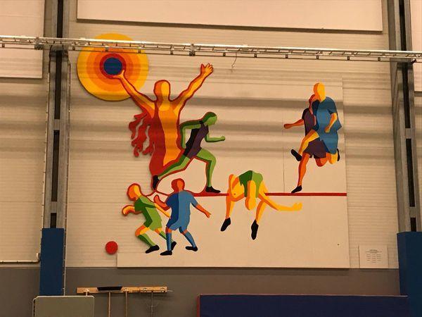 Konstverk på vägg med illustrerade idrottare