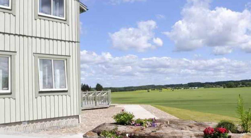 Gaveln på ett tvåvåningshus som vetter mot en härligt grön slätt