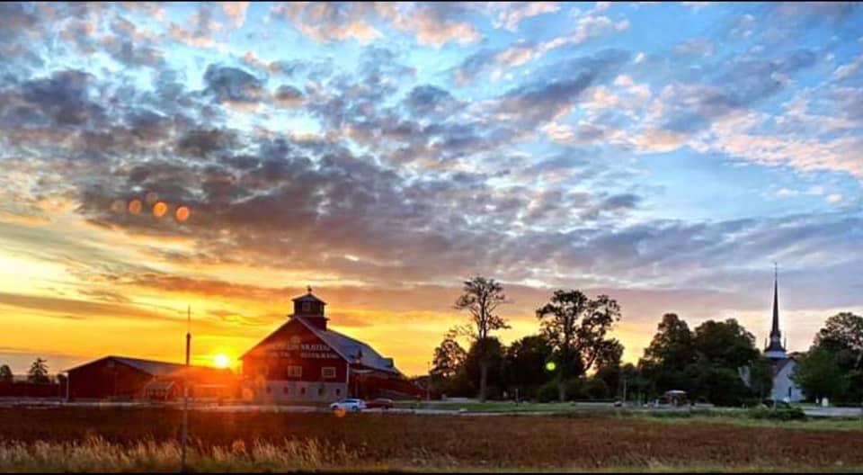 ett fot på en soluppgång med knallblå himmel och ett rödvitt hus i horisonten