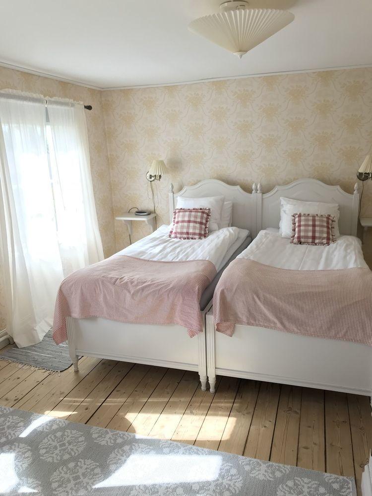 Två sängar som är placerade intill varandra, bäddade med vita och rosa lakan. Solljuset skiner in i rummet trots att en tunn vit gardin skymmer sikten