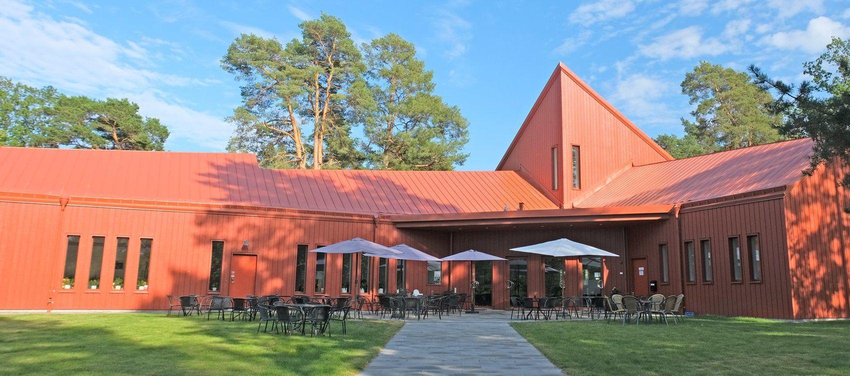 rödfärgad avlång byggnad med många svarta stolar och bord placerade framför byggnaden