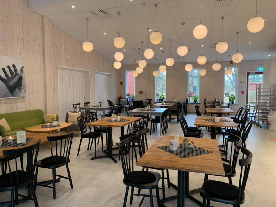 Många små fyrkantiga bord med svarta stolar, i taket hänger ett tjugotal klotrunda lampor, till vänster i bild skymtar en vårgrön soffa.