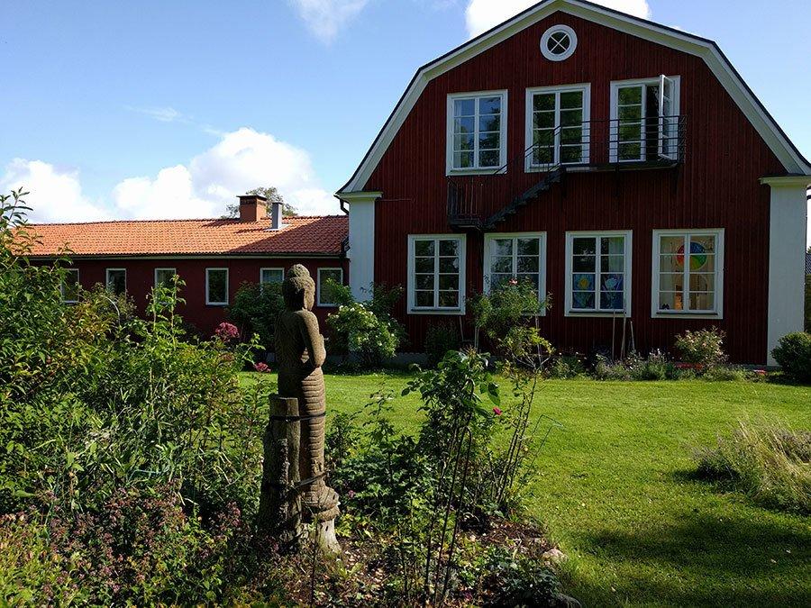En stor maffib rödvit gammal skola med en grönskande trädgård. En stor asiatisk staty ståtar i trädgården.