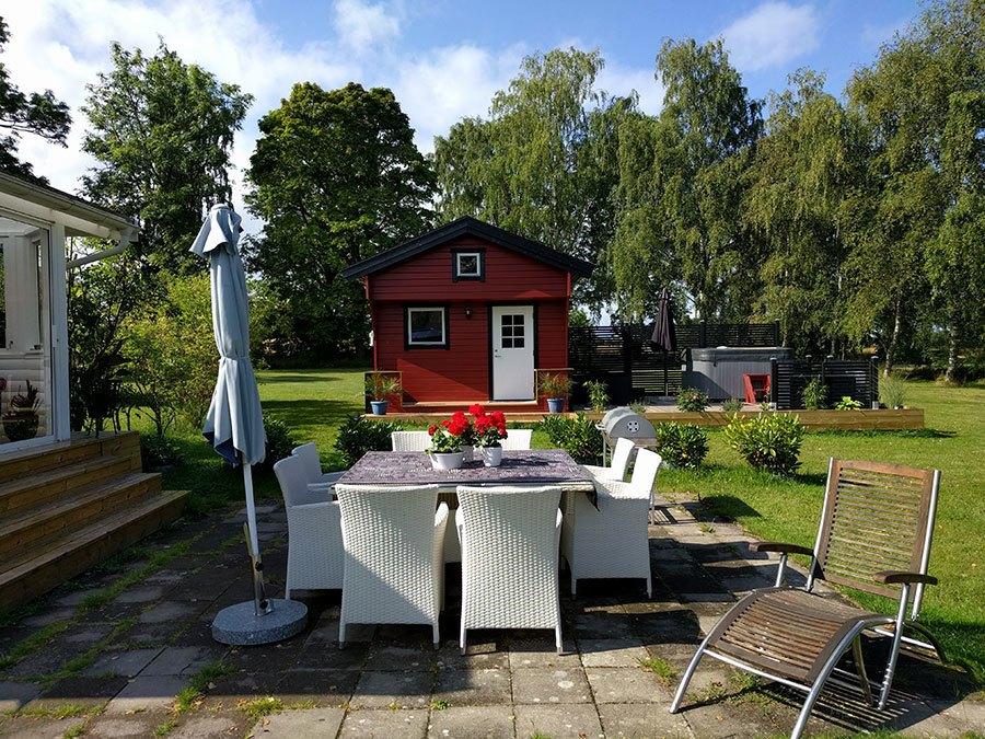 Vita korgmöbelstolar runt ett stort bord ståendes på stenplattor utomhus. I bakgrunden skymtar en liten rödsvart stuga och ett spabad.