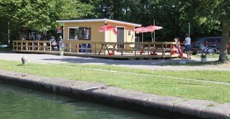 I förgrunden skymtar kanalen, en liten gul glasskiosk är centrerad i bilden utanför den finns en stor träaltan.