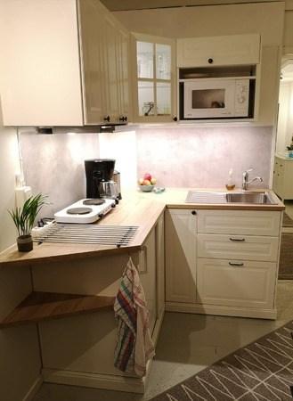 Ett foto som visar en ljus köksbänk med en kokplatta och en skål med olika frukter