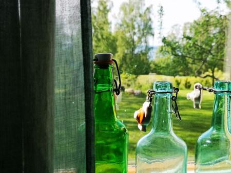 En idyllisk sommarhage skymtar i ett öppet fönster. Två ljusgröna buteljer står placerade i centrum.