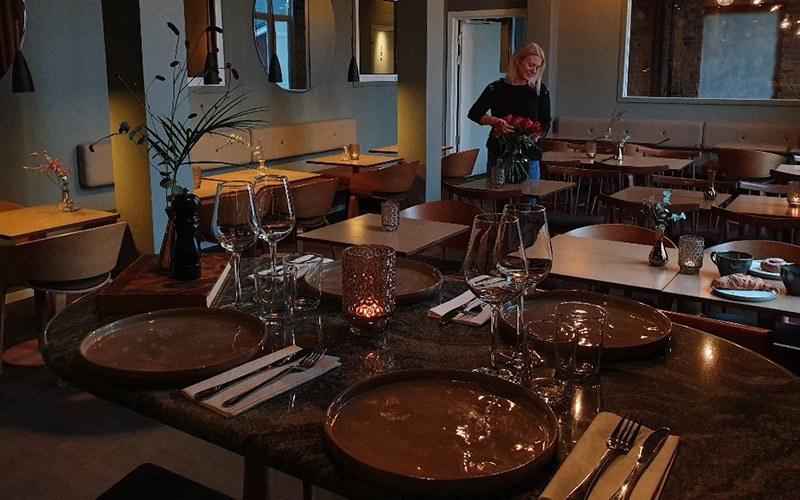 En matsal inredd med dova färger, ett tiotal bord står uppställda där några är dukade och redo att ta emot gäster.