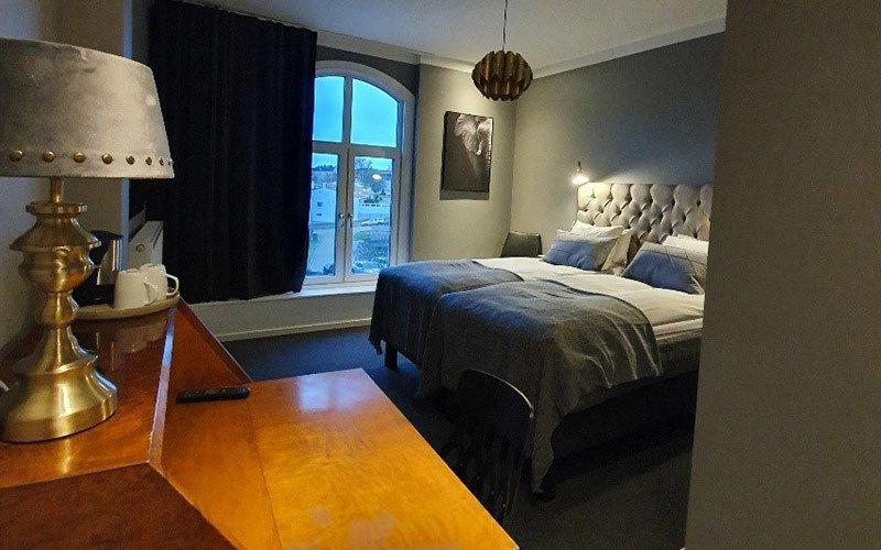 En välputsad träbyrå ståtar framför två välbäddade, inbjudande sängar.
