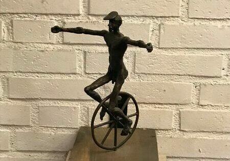 Bronsskupltur i form av man som cyklar enhjuling
