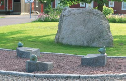 Tre små stenblock med huvuden placerade på ett grusat område. I bakgrunden syns ett stort klibblock.