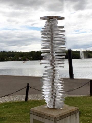 Ett foto på ett konstverk som består av glasskivor placerade ovanpå varandra, sammanfogade med en pelare. I bakgrunden skymtar sjön Vättern.