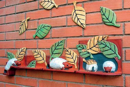 En tegelvägg som har försetts med keramiklöv i gult och grönt, under dessa ligger små djur som påminner om igelkottar med löv som täcken.