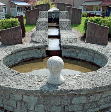 En rund stenbassäng med vatten som har runnit ner för en stentrappa som syns i bakgrunden.